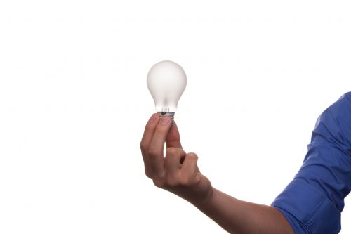 Home electrical safety, man holding light bulb , white background, Lucent Home Inspections